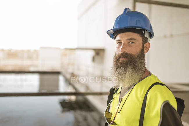 Portrait of bearded worker in factory roof — Stock Photo