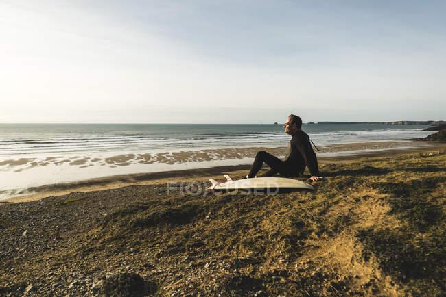 França, Bretagne, Finistere, península de Crozon, homem sentado na costa com prancha — Fotografia de Stock