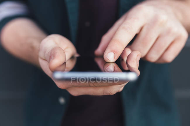 Cropped image of person holding smartphone with blank screen — Stock Photo