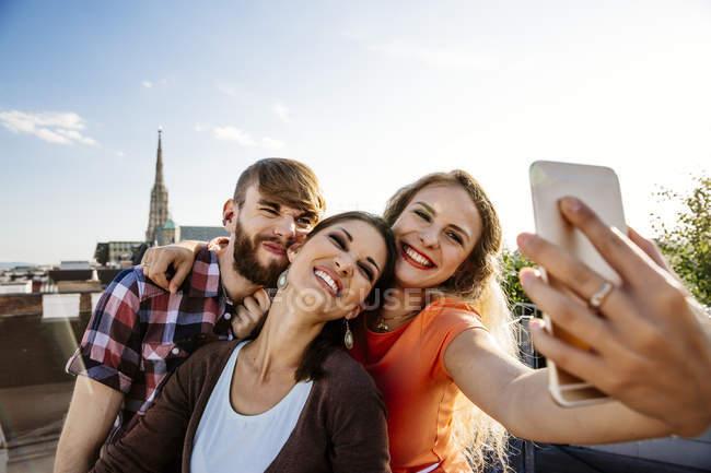 Österreich, Wien, drei Freunde nehmen Selfie auf Dachterrasse mit Stephansdom im Hintergrund — Stockfoto