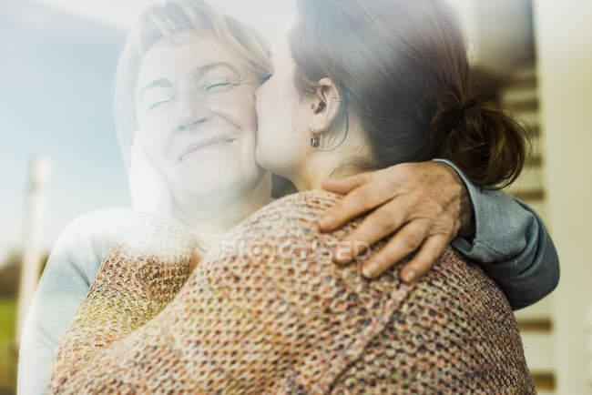Young woman kissing senior woman behind windowpane — Stock Photo