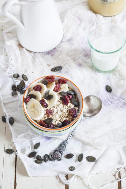 Чаша вівсяних пластівців з сушеної журавлини, бананові шматочки і насіння гарбуза — стокове фото