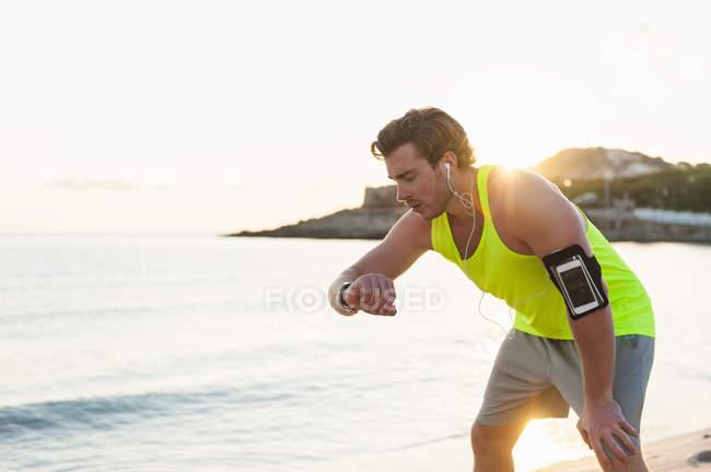 Бігун, дивлячись на smartwatch на пляжі в підсвічуванням — стокове фото