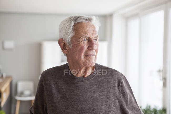Portrait of pensive senior man at home — Stock Photo