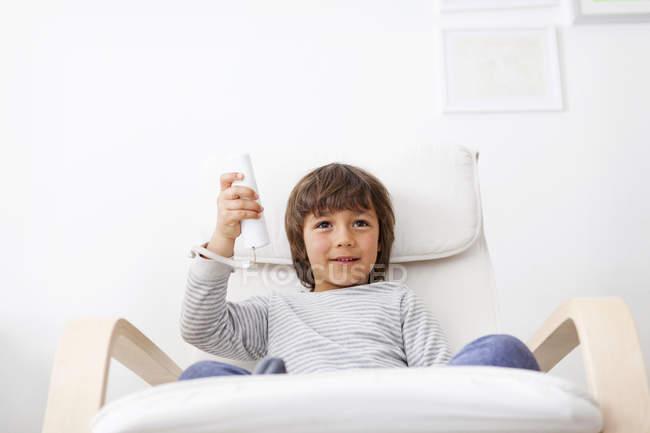 Porträt von kleiner Junge sitzt auf einem Sessel Videospiel — Stockfoto