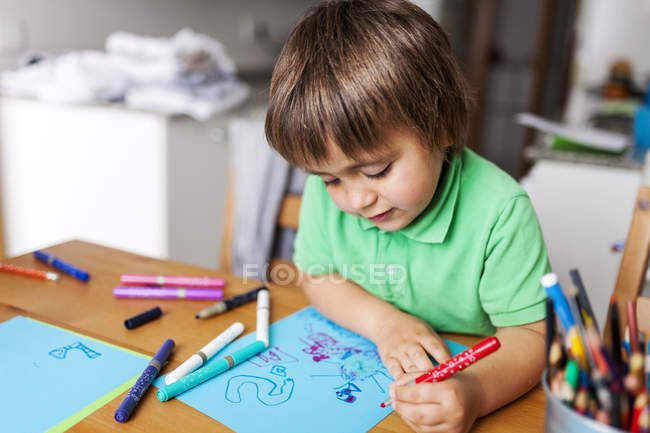 Little boy drawing on blue paper at home — Stock Photo