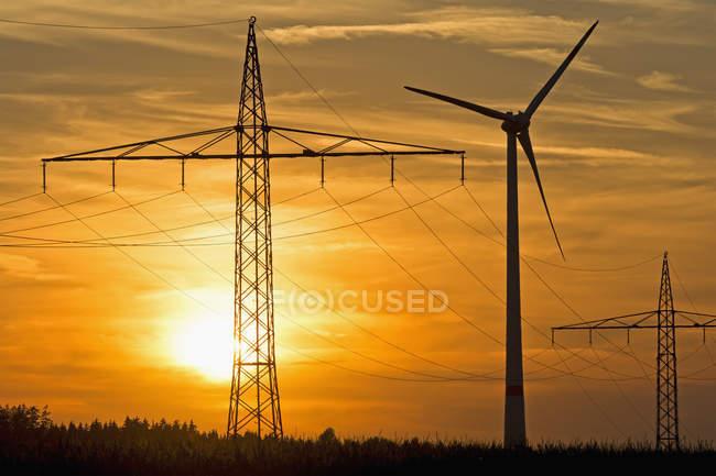 Pylônes de puissance et la roue éolienne et le soir soleil, Bavière, Allemagne — Photo de stock
