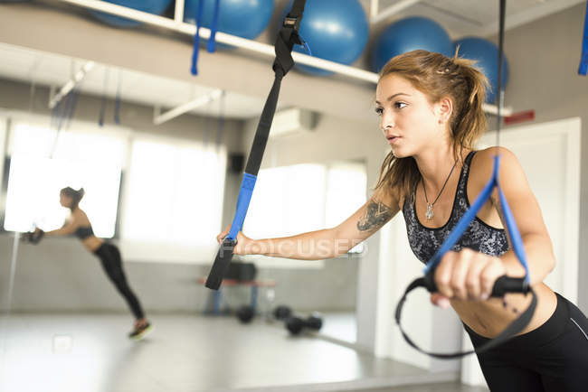 Young woman doing suspension training in gym — Stock Photo