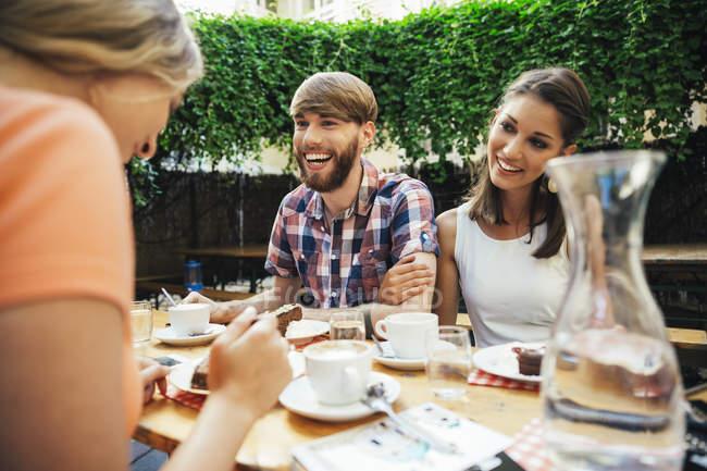 Joyeux jeune couple avec un ami assis à l'extérieur prendre du café et du gâteau — Photo de stock