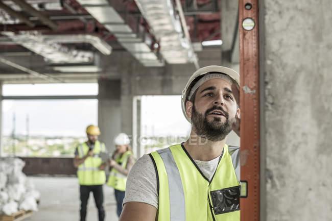 Строительный рабочий, с использованием уровня воды в строительной площадки — стоковое фото