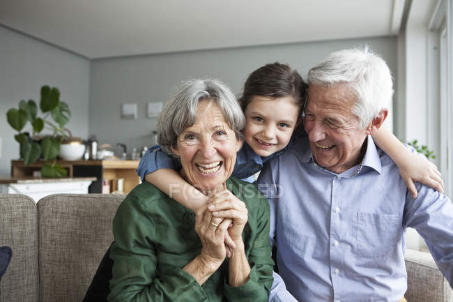 Family portrait of grandparents and their granddaughter at home — Stock Photo