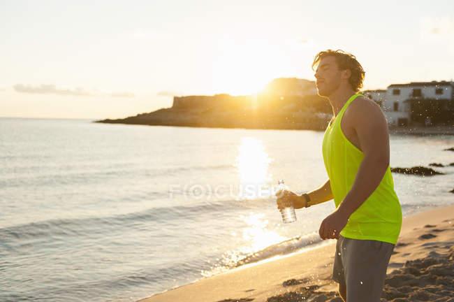 Corredor com garrafa de água que está na praia de manhã — Fotografia de Stock