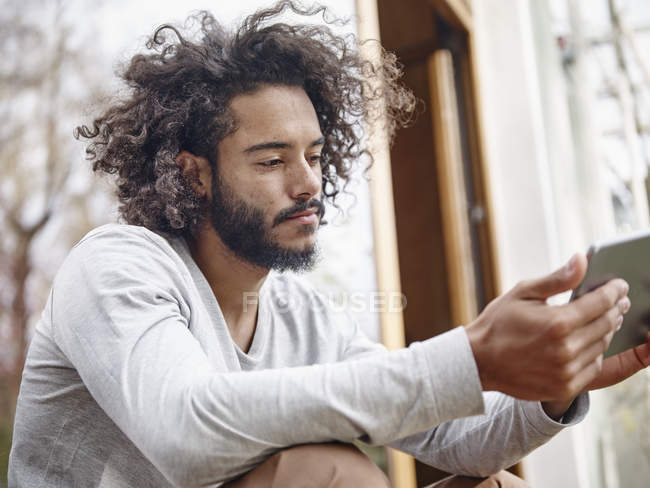Young man looking at digital tablet outdoors — Stock Photo