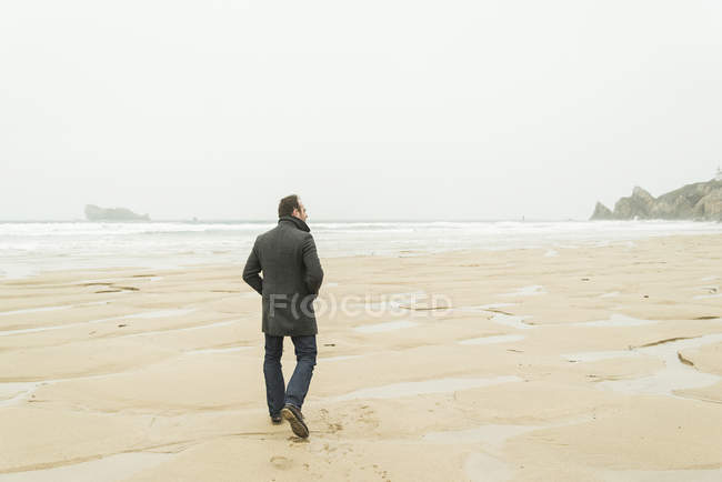 Man walking on the beach with hands in pickets — Stock Photo
