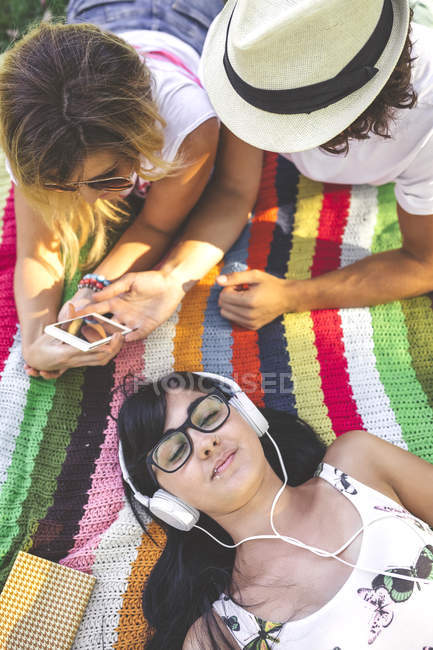 Young woman with friends lying on blanket listening to music — Stock Photo