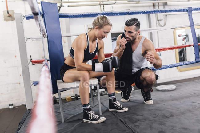 Trainer im Gespräch mit Boxerin im Boxring — Stockfoto