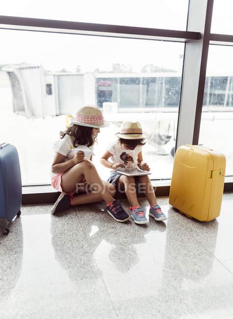 Dos niñas esperando en el aeropuerto, jugando con tableta digital - foto de stock