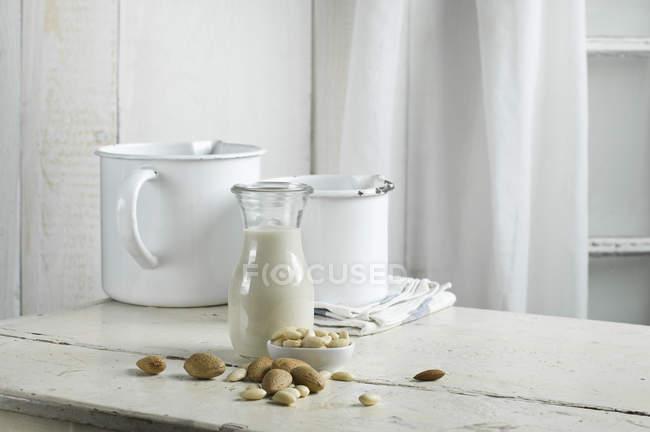 Веганское миндальное молоко в кувшине на столе — стоковое фото