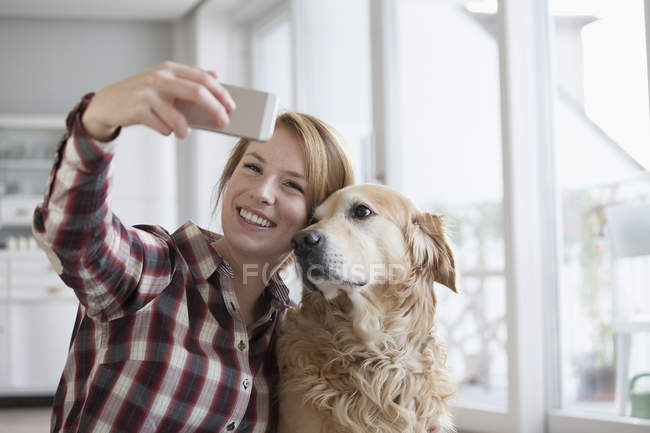 Woman taking a selfie with dog — Stock Photo