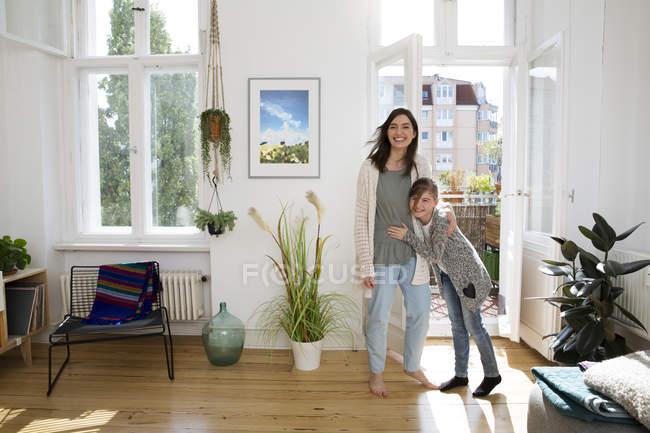 Beautiful caucasian brunette woman hugging daughter at home — Stock Photo