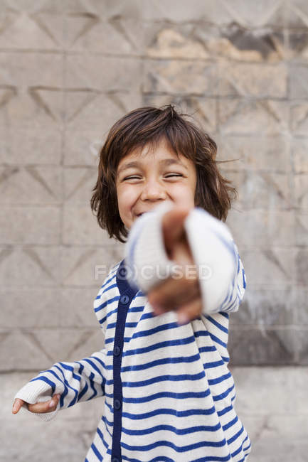 Portrait of laughing little boy pointing on viewer — Stock Photo
