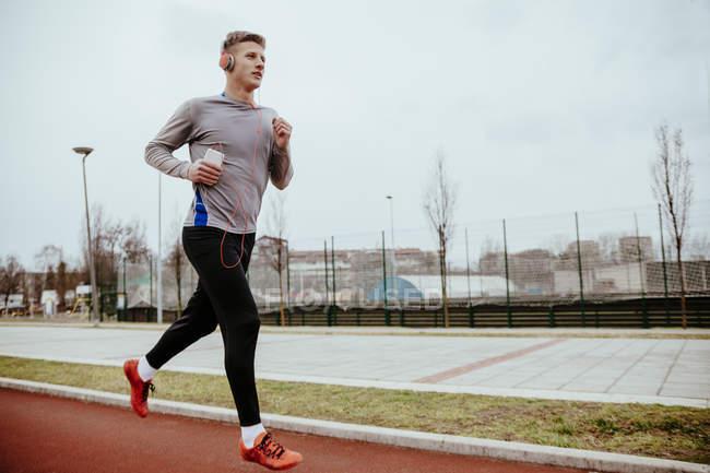 Young man running on tartan track — Stock Photo