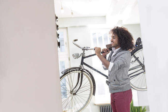 Smiling young man carrying bicycle — Stock Photo