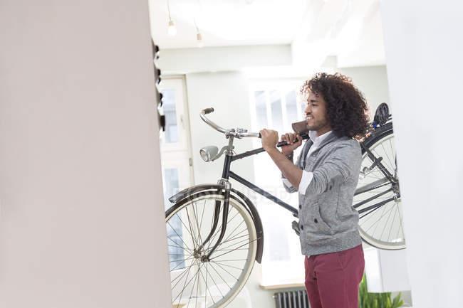 Sonriente a joven llevar bicicleta - foto de stock