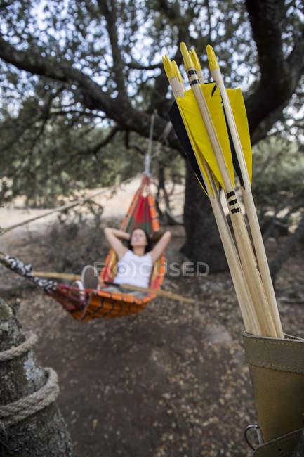Pfeile einer jungen sportlichen Bogenschützin, die auf einer Hängematte im Hintergrund ruht — Stockfoto