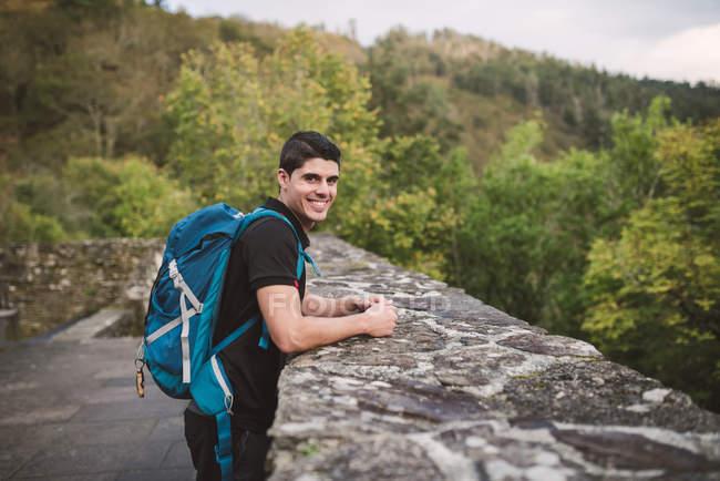 Caminhante homem de pé perto da parede de pedra e olhando para a câmera — Fotografia de Stock