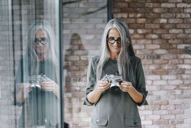 Woman with long grey hair holding camera — Stock Photo