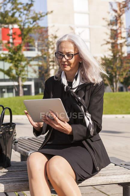 Модні підприємець, сидячи на лавці, за допомогою планшетного — стокове фото
