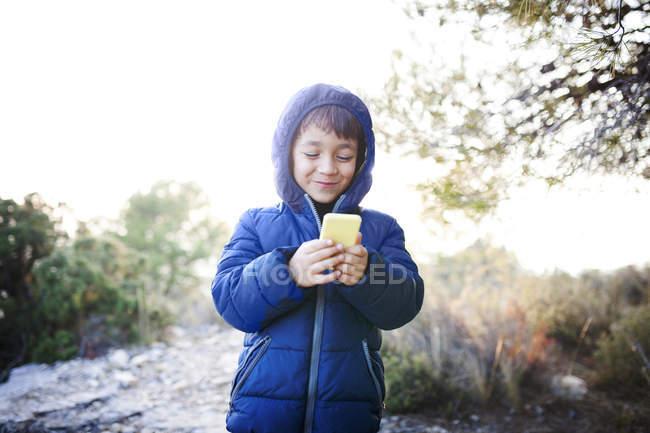Porträt eines lächelnden kleinen Jungen, der auf sein Smartphone blickt — Stockfoto
