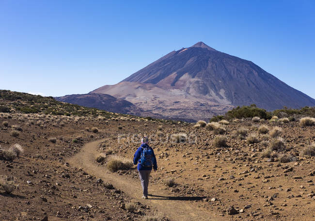 Spain, Canary Islands, Tenerife, Roques de Garcia, Mount Teide, Teide National Park, Female hiker on hiking trail Ruta Arenas Negras — Stock Photo