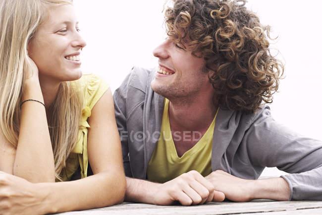 Lächelndes junges Paar auf einem Steg liegend — Stockfoto