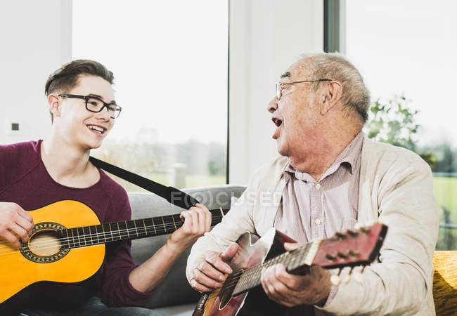 Senior singt und spielt mit Enkel Gitarre — Stockfoto