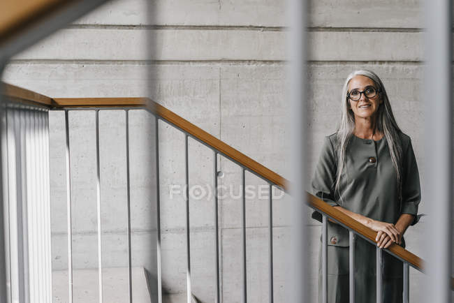 Portrait of smiling woman with long grey hair standing on staircase — Stock Photo