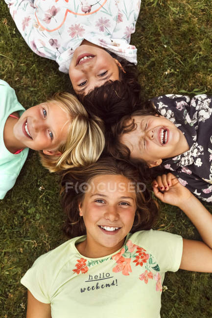 Four little girls lying on the grass — Stock Photo