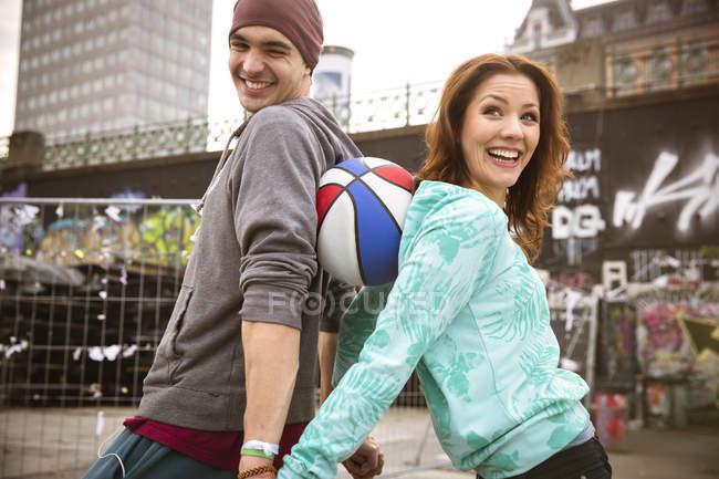 Giovani coppie felici a scherzare con tempo libero basket — Foto stock