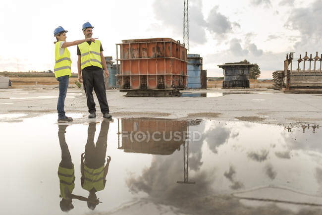 Man and woman in safety vests on industrial site — Stock Photo