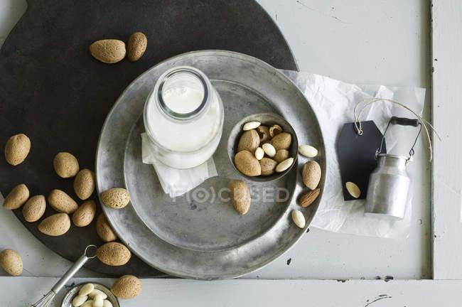 Стеклянная бутылка домашнего миндального молока и миндаля — стоковое фото