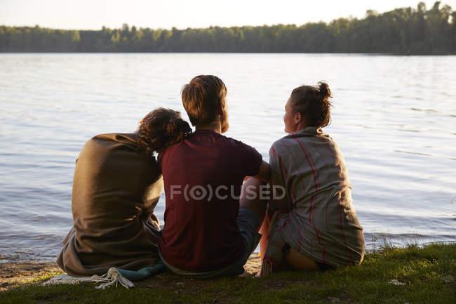 Friends sitting at a lake enjoying sunset — Stock Photo