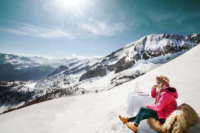Mujer joven sentada a la mesa en las montañas - foto de stock