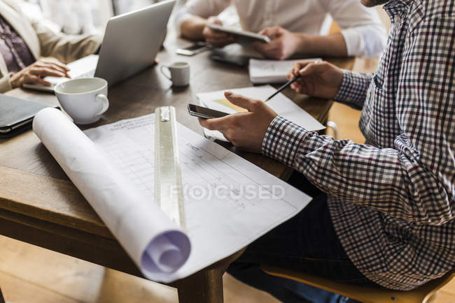 Cropped image of colleagues at desk with smartphone, laptop and construction plan — Stock Photo