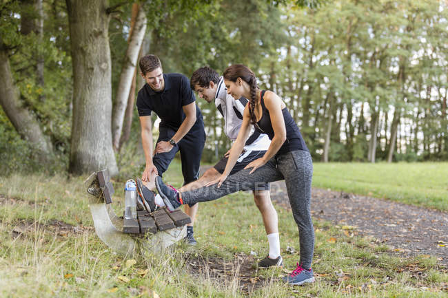 Athletes stretching on a park bench — Stock Photo