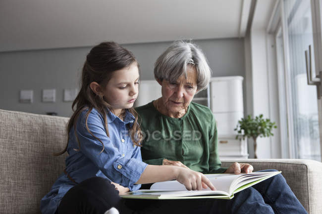Grandmother and her granddaughter sitting together on the couch with a book — Stock Photo