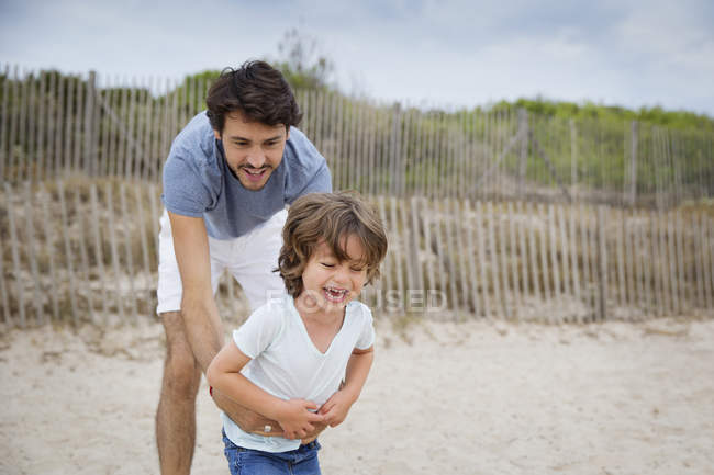 Father and son playing together on the beach — Stock Photo
