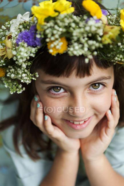 Portrait of smiling little girl wearing flowers — Stock Photo