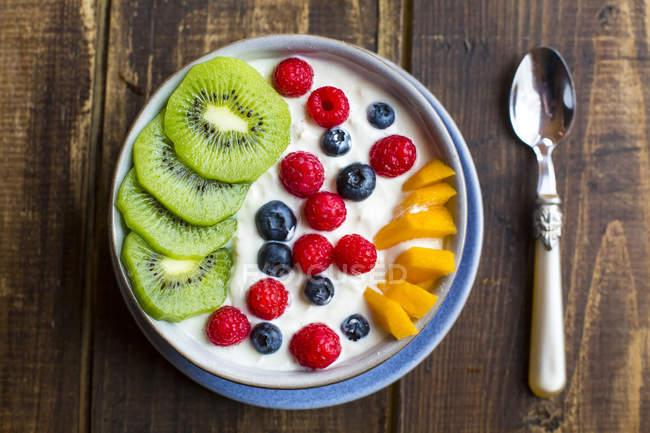 Ciotola con yogurt e mirtilli, kiwi, mango e lamponi, cucchiaio di legno — Foto stock