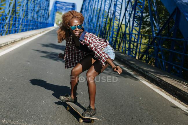 Giovane donna sullo skateboard su un ponte — Foto stock